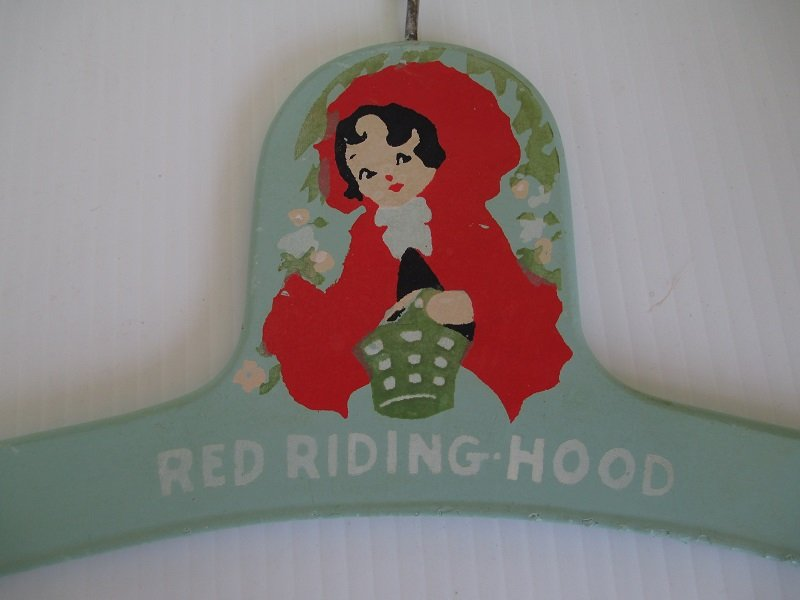 Set of 2 wood hangers for baby clothes. One with a baby's face, one with Little Red Riding Hood. Estimated time frame of 1920s to 1940s.