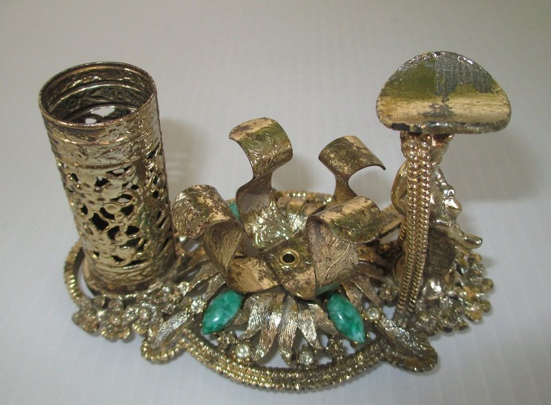 Vintage 1950s lipstick fingernail polish holder with finger rest from SF Sam Fink. Highlighted with green stones, rhinestones, and a cherub.