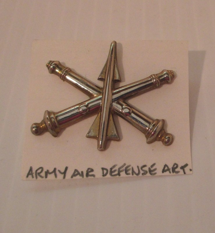 U.S. Army Officer metal insignia Badge for the Air Defense Artillery. Has crossed cannons. Marked Simon G.I. on back. Worn on Army Uniforms and caps.