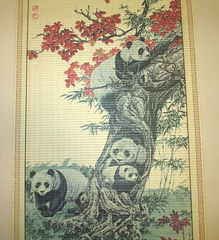Pandas enjoying a peaceful day. Plenty of bamboo close by and relaxation in a hollowed out tree. Scroll wall hanging measures 12.5 by 33 inches.