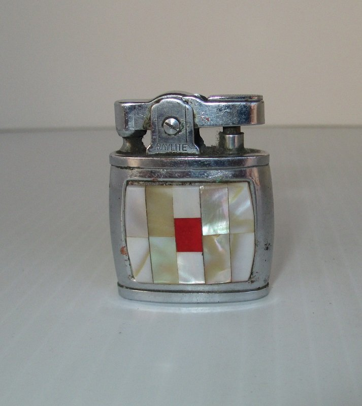 1950s 1960s Art Deco style Raylite Lighter. Front features Mother of Pearl squares. Known as Baby Style and made in Japan. 1.5 inches tall.