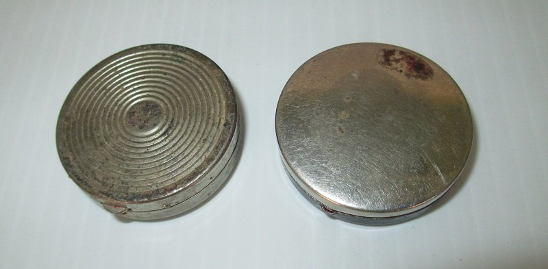 Back side of 1930s rouge compacts. Both have rouge remaining and a mirror. One has  an applicator. One Elizabeth Post, the other is unmarked.