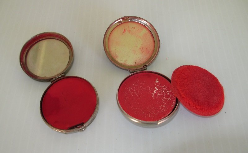Inside of 1930s rouge compacts. Both have rouge remaining and a mirror. One has  an applicator. One Elizabeth Post, the other is unmarked.
