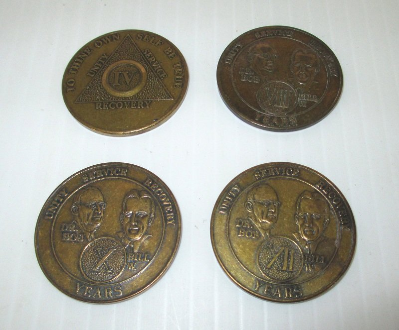 Four achievement tokens representing various years of alcohol free living. One each for 4 years, one for 8 years, one for 10 years, and one for 12 years.