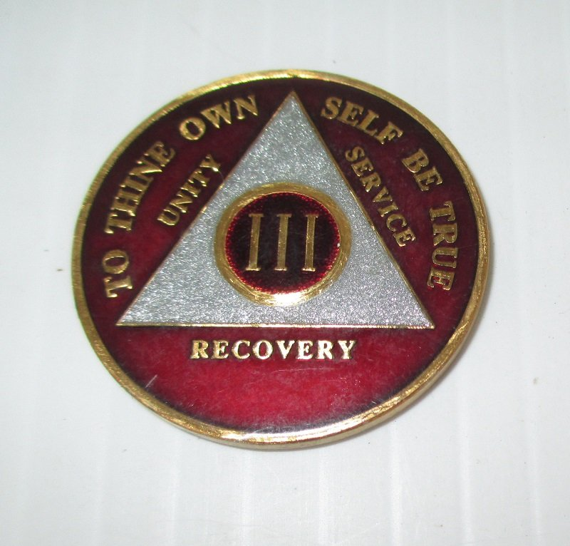 Achievement token for 3 years alcohol free living. Burnt red color with gold and silver highlights. Back is black with serenity prayer. Enamel finish.