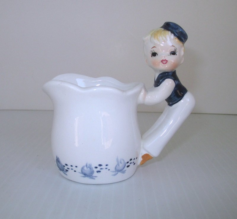 Vintage creamer from the 1950s. Enesco Dutch Treat pattern. Dutch girl or pixie as the handle. Enesco sticker and marked number E-5817.