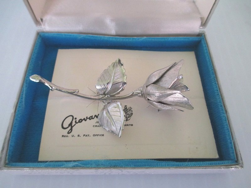 Legend of the Christmas Rose brooch. Silver color 2.75 inches long. Comes in original Giovanni box with story card in poem verse. Dated 1966.