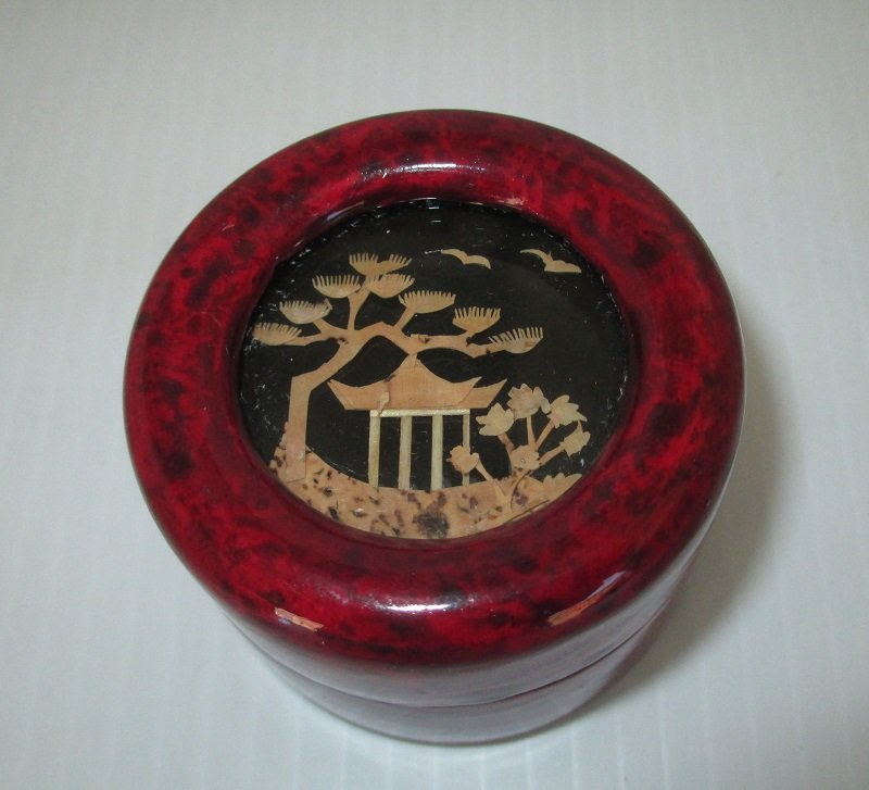 Chinese jewelry trinket box, shadow box type. Small in size. Top features a Chinese building made from bamboo shavings. Red lacquered.