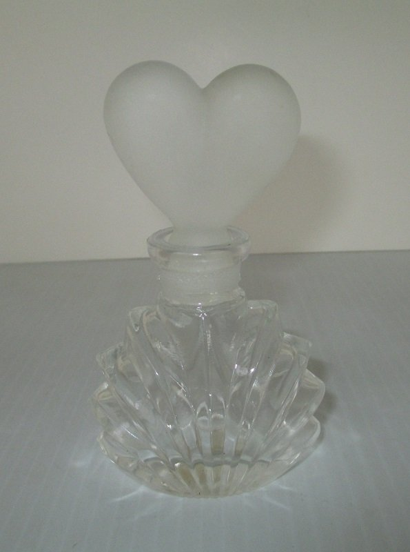 4.25 inch tall perfume bottle with I.W. Rice sticker on bottom. Frosted ground glass heart shaped stopper.  Unknown date. The bottle is empty.