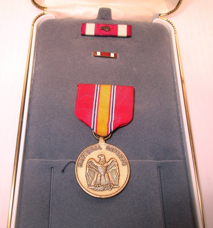 Unmatched military award set consisting of a National Defense Medal plus an unknown ribbon bar and lapel pin. Comes in a plush leather case.