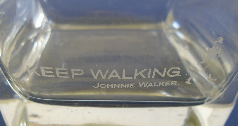Johnnie Walker whiskey bar glass. 3.5 inches tall with white etching of 'Keep Walking' logo and man in top hat and coat tails.
