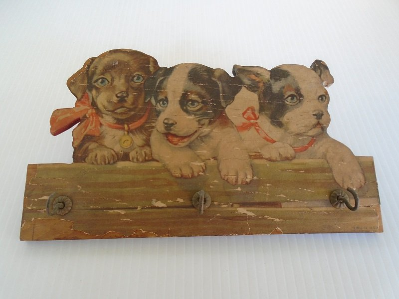 3 puppies highlight this antique wall plaque. Has 3 hooks for hanging small items such as keys, lanyards, etc. Made of wood with litho. circa 1930s.
