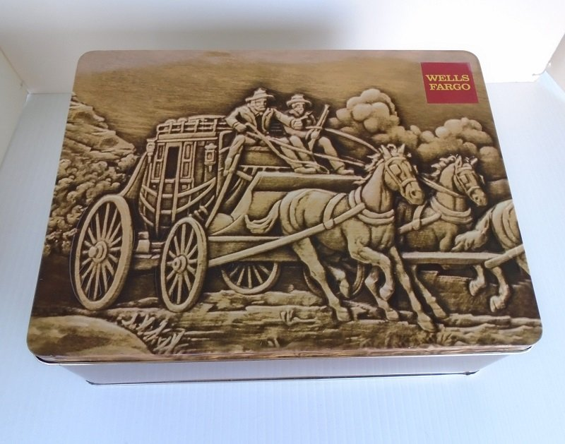 1980s collectible cookie tin featuring the Wells Fargo stagecoach, horses, and drivers travelling across the prairie. 10.5 x 8 x 3.75 inches.
