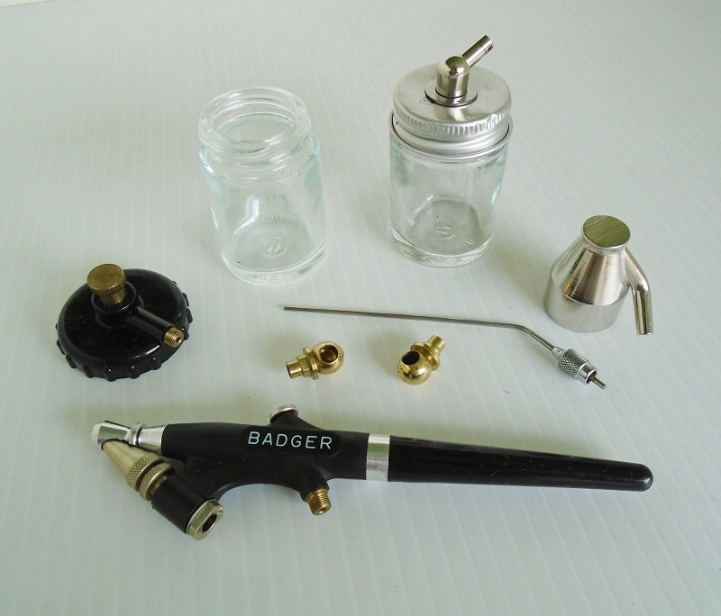 Various pieces of a Badger 350 Air Brush set. Includes the air brush, bottles and extra caps, nozzles, etc. Not a complete set. Offered by kenoticket
