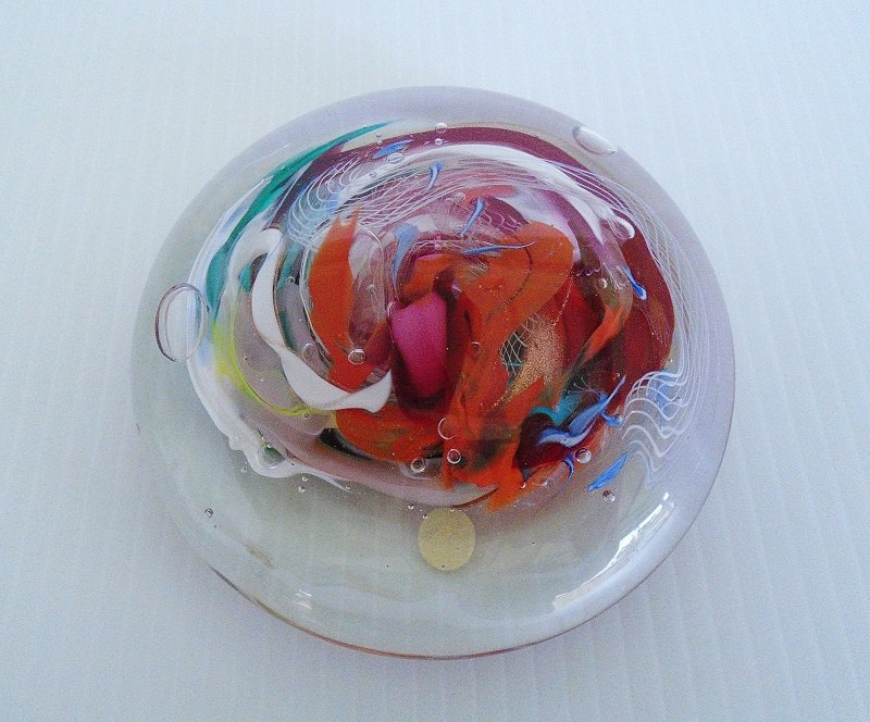 Various colors in a swirl pattern are in the center of this flat sphere glass paperweight. 4.75 inches side to side, 1.5 inches tall. Unknown date.