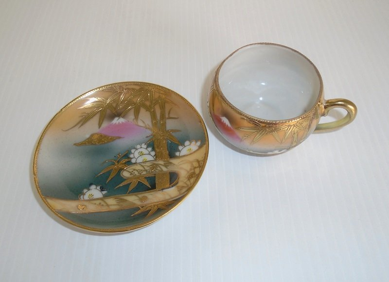 Rare antique circa 1920s to 1930s demitasse or tea cup and saucer. Has mountain and tree scene. Marked des.pat Made in China. Main color of gold.