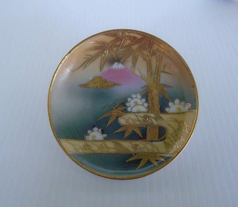 Rare antique circa 1920s to 1930s demitasse or tea saucer. Has mountain and tree scene. Marked des.pat Made in China. Main color of gold.
