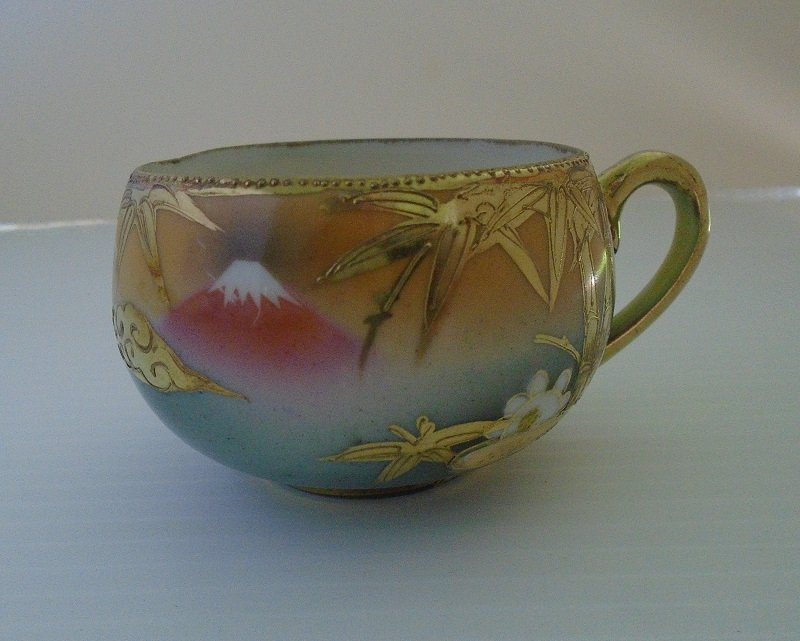 Rare antique circa 1920s to 1930s demitasse or tea cup. Has mountain and tree scene. Saucer marked des.pat Made in China. Main color of gold.
