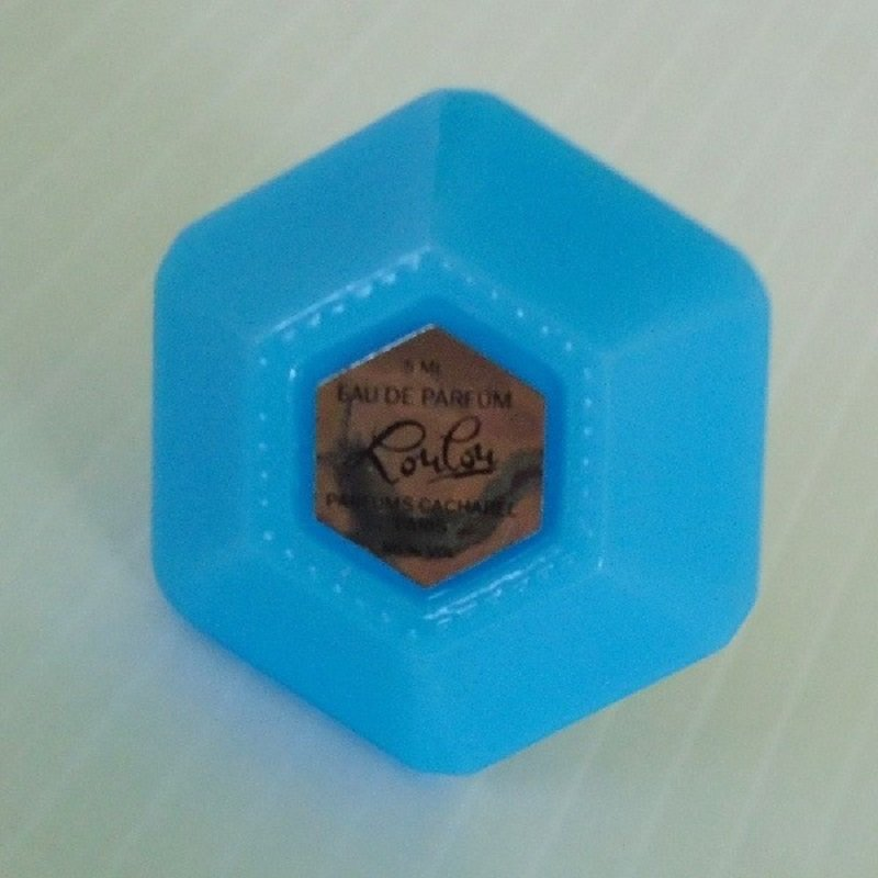 Empty mini perfume bottle that once held 5ml of Lou Lou. Made by Cacharel Paris. Bottle resembles an ink well. Turquoise blue and burnt red colors