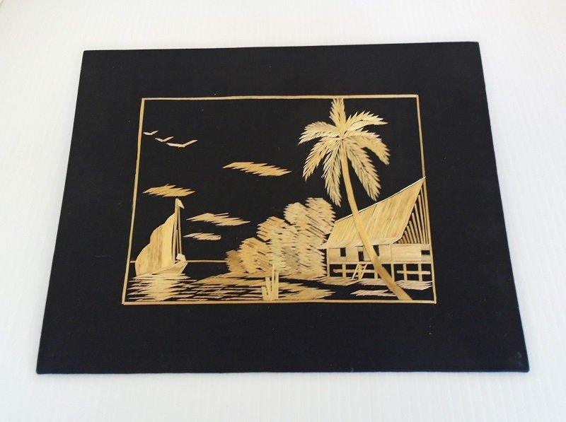 Handmade Asian art. Straw or Bamboo on black silk. Estimated 1950 to 1960 decade. 8.5 by 11 inches. House, water, birds, palm tree.
