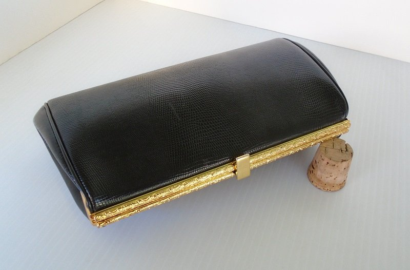 Leather Etienne Aigner vintage 1970s black clutch purse. Snake embossed with gold color hardware. Hide-a-way 5 inch drop chain strap.