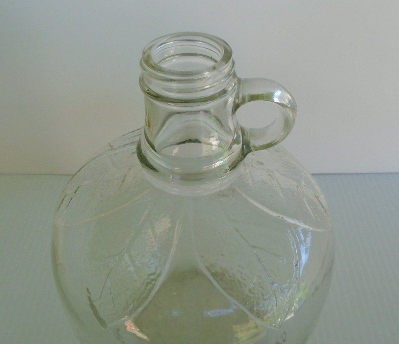Drink Your Apple A Day vintage 1930s to 1950s Martinelli & Co. Apple Cider Jug. 1/2 gallon capacity. Clear glass. Decorated with leaves.