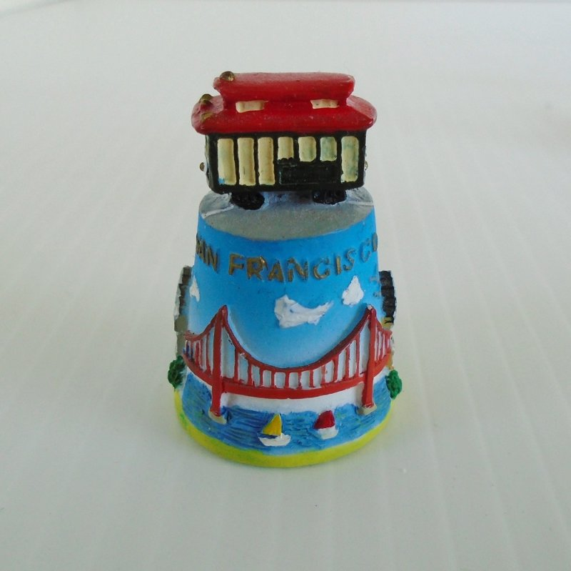 Collectible souvenir thimble from San Francisco California. Features Golden Gate Bridge, Victorian homes, tall buildings. Topped with a red cable car.