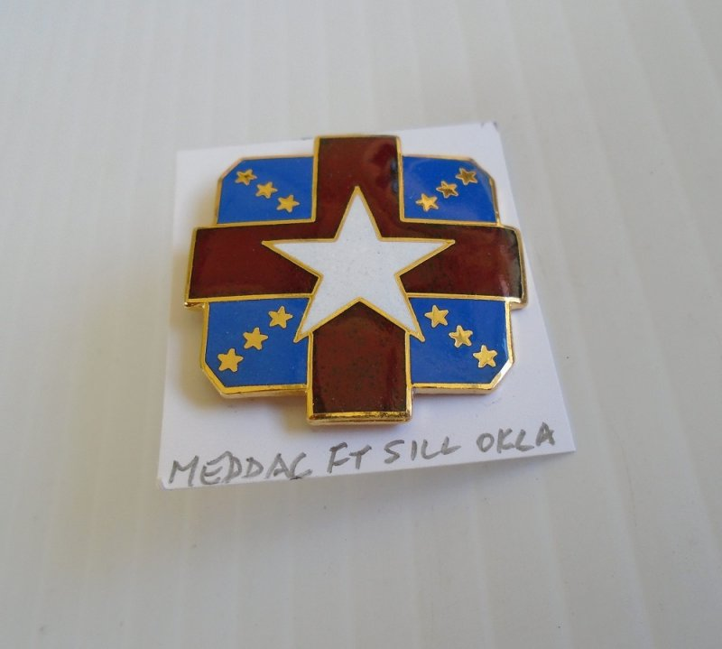 Insignia pin for U.S. Army Fort Ft. Sill Oklahoma MEDDAC. Enameled. Burgundy, blue, white, and gold in color. Measures 1-1/8 inch. Worn on uniforms.
