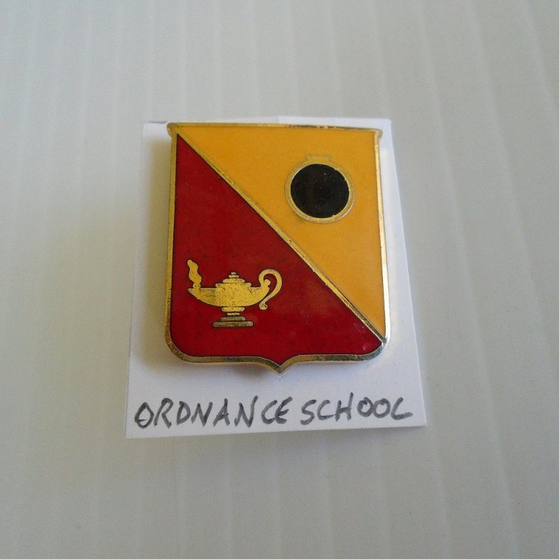 Insignia pin for U.S. Army Ordnance School. Unknown age, but older. Shows a cannon ball and a lantern. Worn on uniforms.