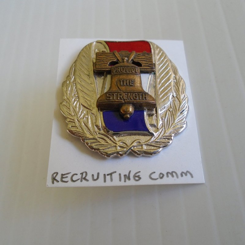 Insignia pin for U.S. Army Recruiting Command. Features the Liberty Bell. Says 'Provide The Strength' in the center. Worn on uniforms.