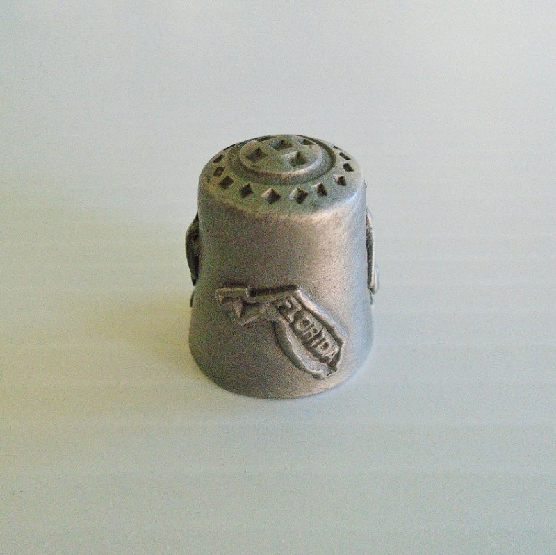 Collectible souvenir pewter thimble for the state of Florida. Signed Gish (for Nicholas Gish). 1 inch tall. Pelican, palm tree. Unknown age.