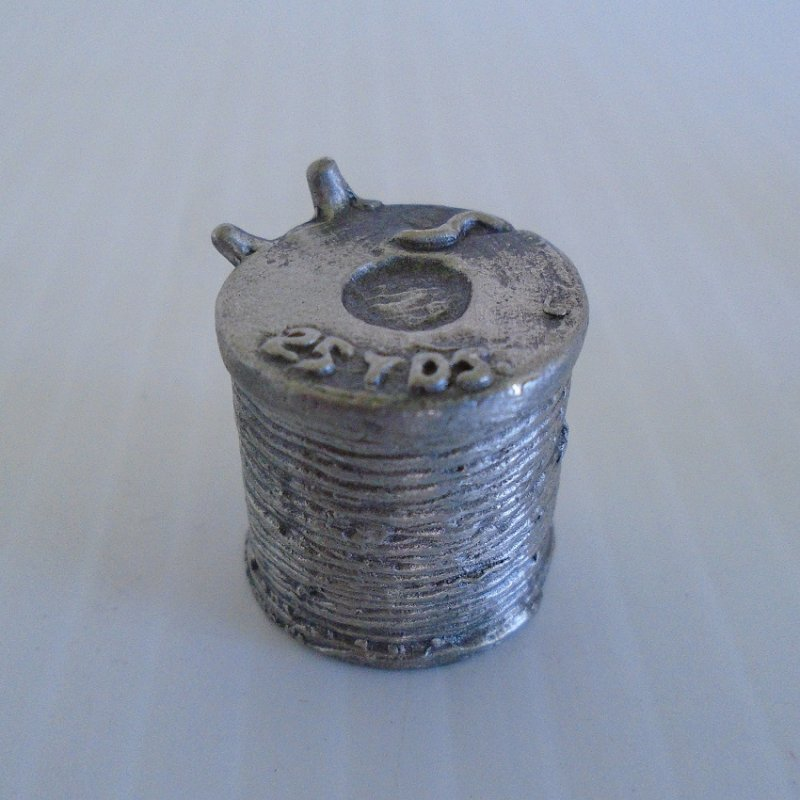 Collectible souvenir pewter thimble shaped like a spool of thread with needles sticking in the side. Unknown age. Most likely Nicholas Gish.