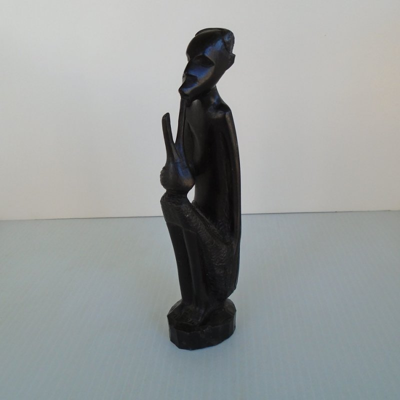 Circa 1960s hand carved African art sculpture of a man smoking a pipe. Made of dark wood with sticker stating