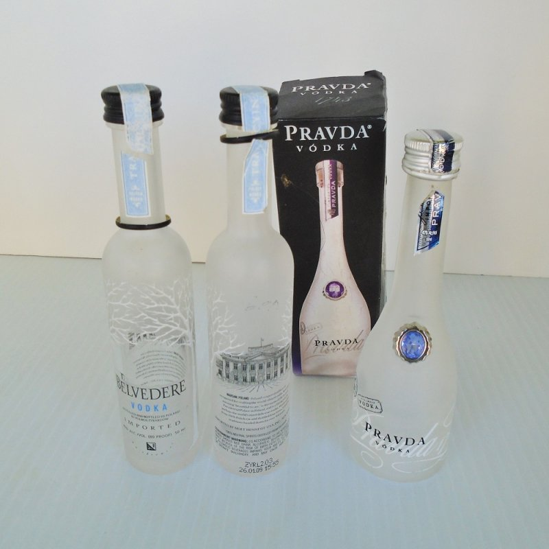 Three empty miniature vodka bottles, 2 were Belvedere, one was Pravda. Both from Poland. Various possible uses.