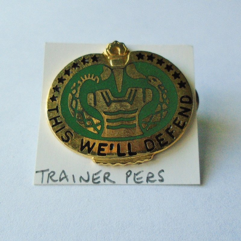 Insignia DUI pin for U.S. Army Trainer Personnel group. Green and gold. Six pins available with different marks on the back. Worn on uniforms.