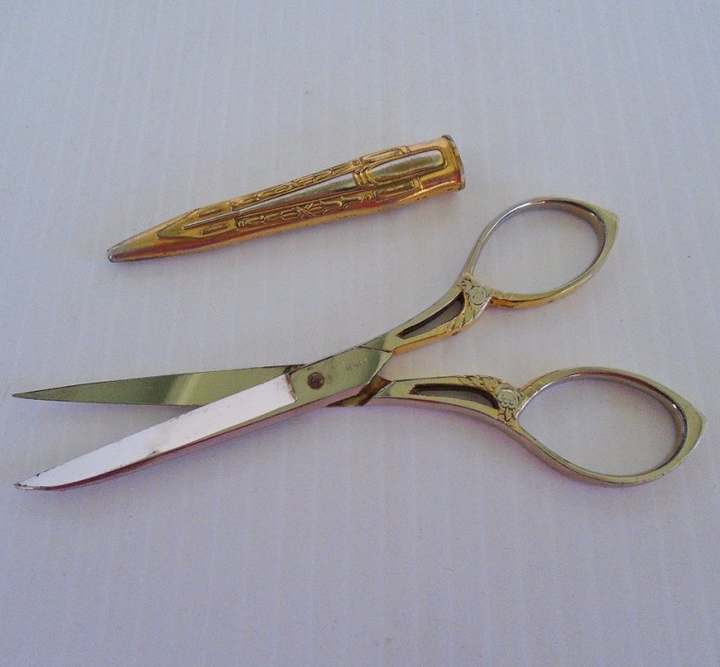 Gold plated embroidery scissors marked SMF Solingen and Germany. Has a small etching of a king in a sitting position. Vintage estate purchase.