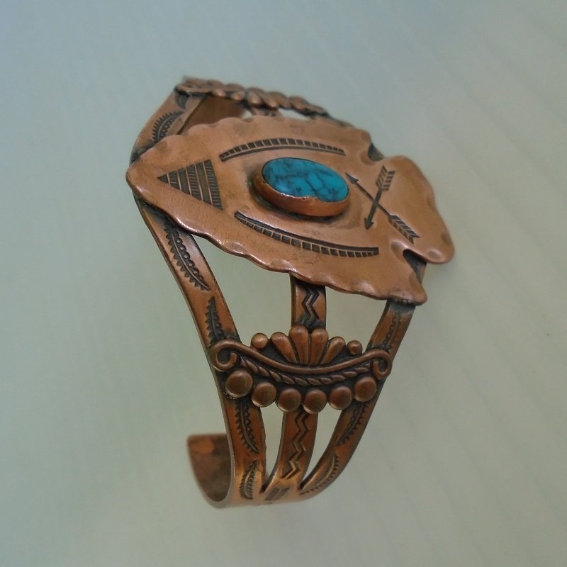 Copper and turquoise cuff bracelet made by the Bell Trading Company and sold along old Route 66 in the 1950s. Features an arrowhead design.