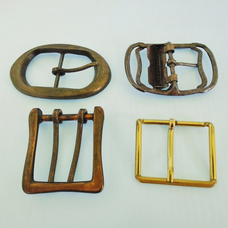 Lot of 4 vintage brass belt buckles. One is military type, one is double pronged, two are standard. Two marked with a letter W. Estate purchase.