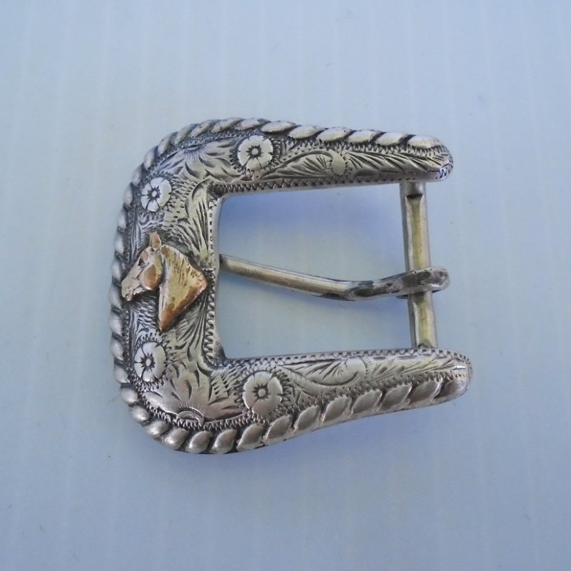 Vintage 1930s to 1940s Sterling Silver belt buckle with 14k gold plated horse head. Also has etched flowers. Measures about 1.75 inches.