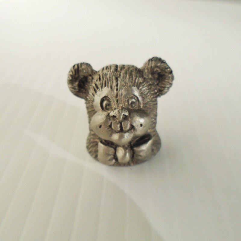 Souvenir pewter thimble featuring a teddy bear head. The bear is smiling and is wearing a bow tie. Signed Spoontiques and dated 1982.