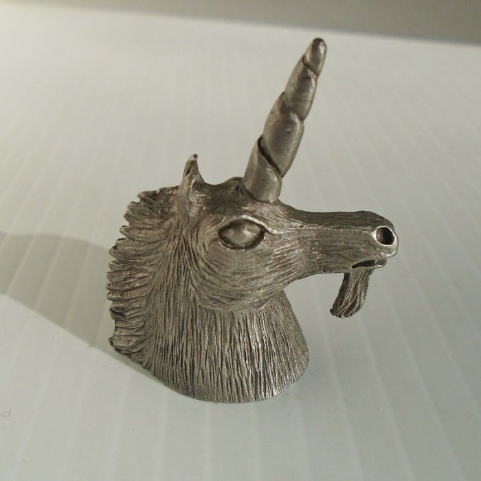 Souvenir pewter thimble featuring a Unicorn head. It stands 1.75 inches tall and its side is signed Spoontiques and dated 1980.