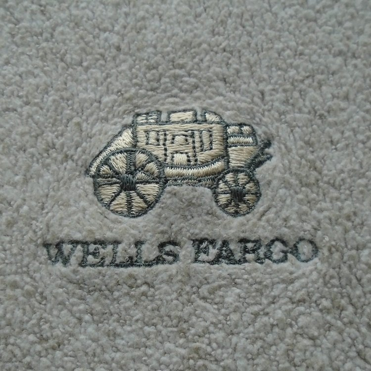 Wells Fargo Bank tan fleece pullover shirt. Long sleeves. Size XL. Has stagecoach logo on left breast.