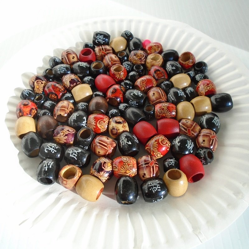 Wood barrel beads in colors of tan red, coffee, and black with white Asian writing. Total of 94 beads with various designs. 1/2 to 1/4 inch, large hole.