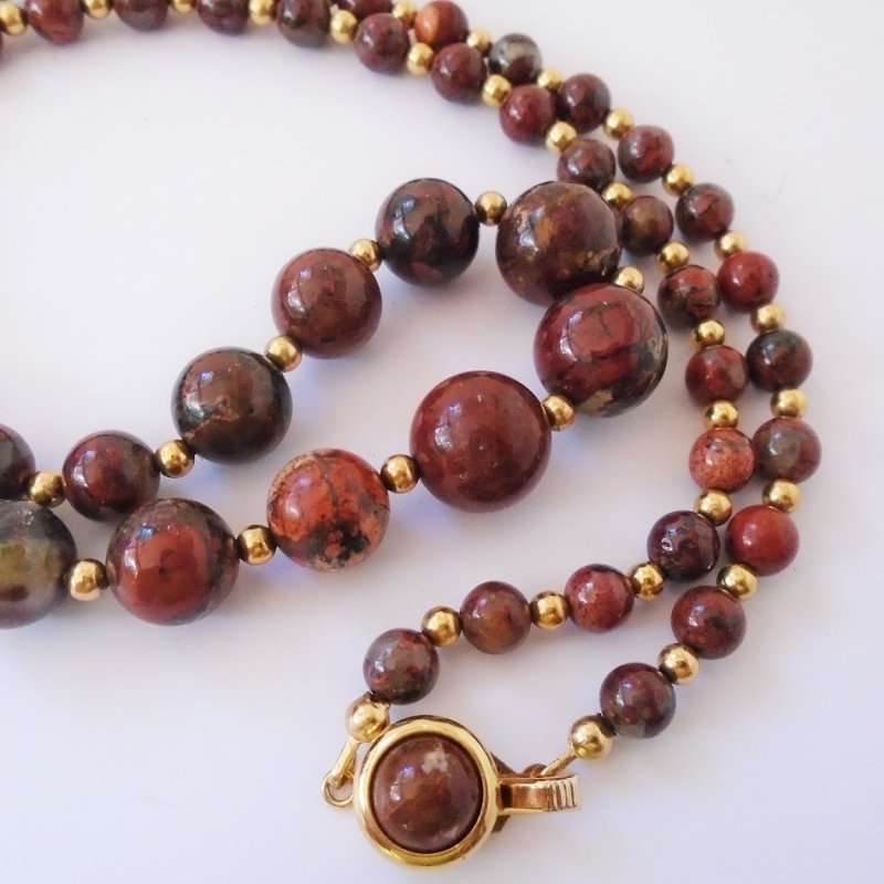 Beaded necklace, brown with red, gray, and butterscotch marbling. 24.5 inches long. Possibly made of marble. Possibly 1970s to 1980s. Estate find.