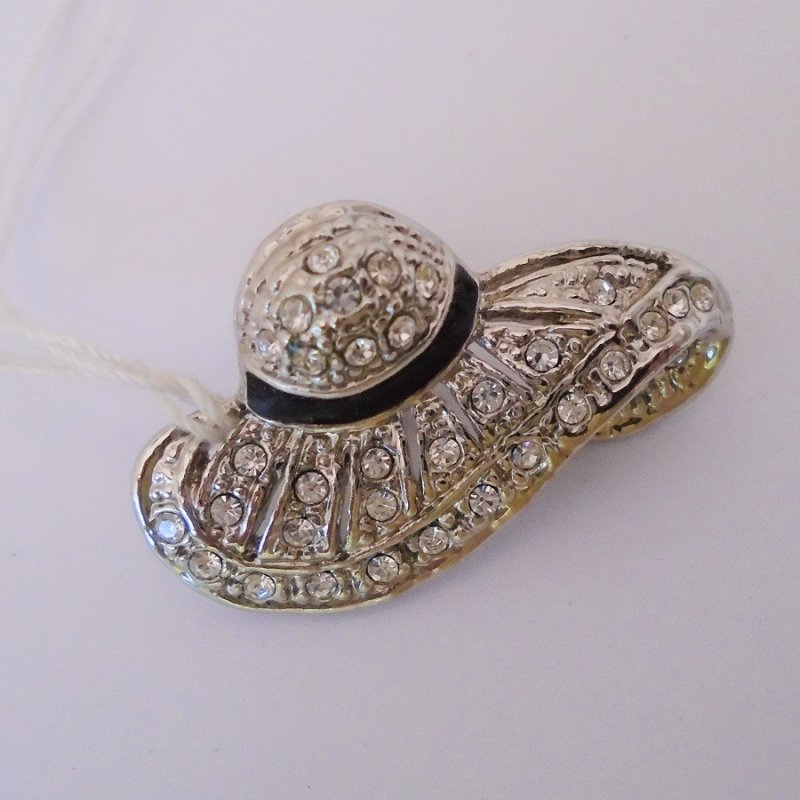 Very classy pin brooch in the design of a hat or possibly a bonnet. Silver in color with many rhinestones and a black enamel band. Estate purchase.