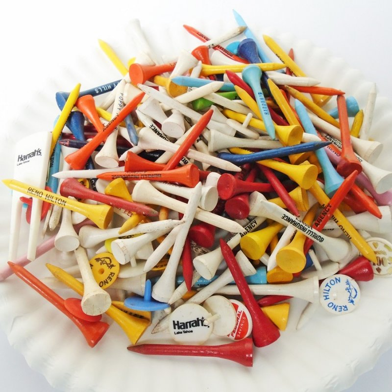 Various golf tees, ball markers, divot tool. About 188 pieces. Most have various logos from casinos, hotels, companies.