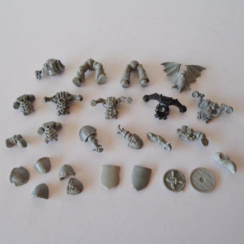 25 misc plastic parts for adding to Warhammer figurines. There are shields, shoulder plates, arms, legs, gear, and even a bat. Looks to be unused.
