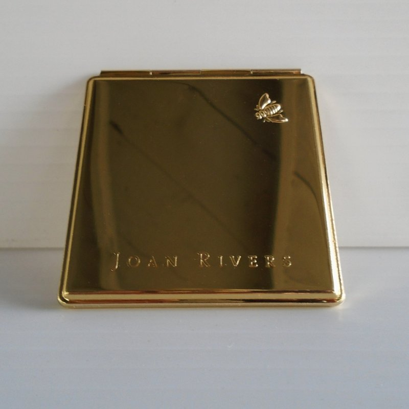 Joan Rivers Compact Mirror. 2.75 inches square. Gold in color with Joan Rivers name and signature Bumble Bee on the front cover. 2 mirrors inside.