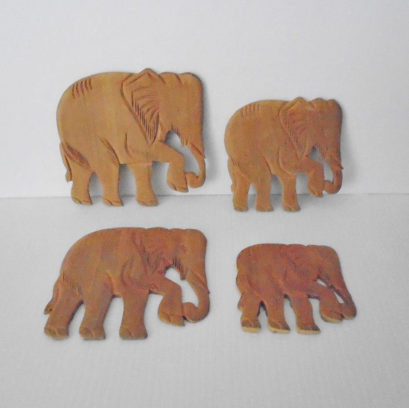 Carved elephant wall plates / plaques. Set of 4. Wood, ranging in size from 3.75 to 5.5 inches.