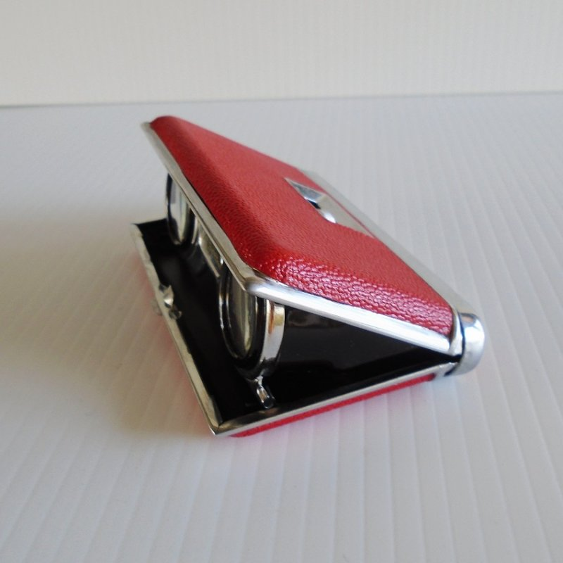 Folding Opera Glasses housed inside a chrome and red leather case. One piece unit from the 1960s. Has focusing ability. Estate find.